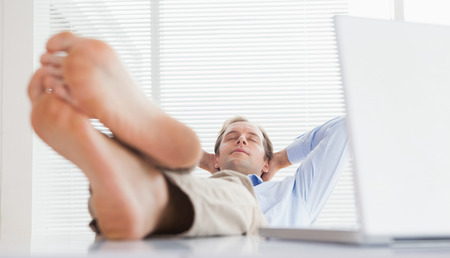 Relaxed businessman with his feet up in his office photo