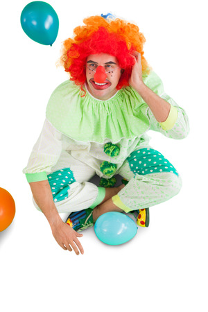 Funny clown sitting on floor on white background photo