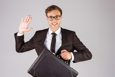 geeky: Young geeky businessman holding briefcase on grey background