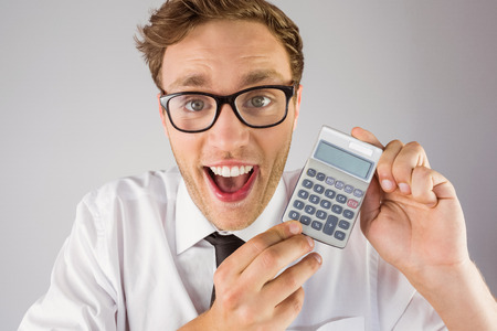 Geeky businessman showing a calculator on grey background photo