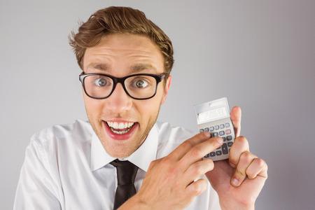 Geeky businessman using a calculator on grey background photo