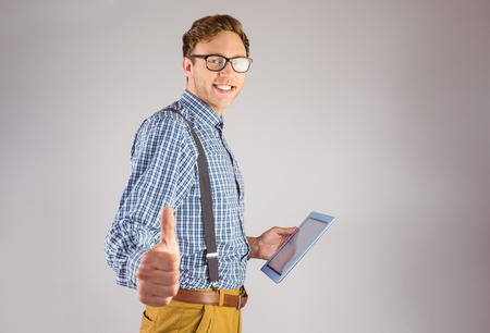 Geeky businessman using his tablet pc on grey background photo