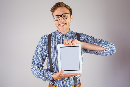Geeky businessman showing his tablet pc on grey background photo