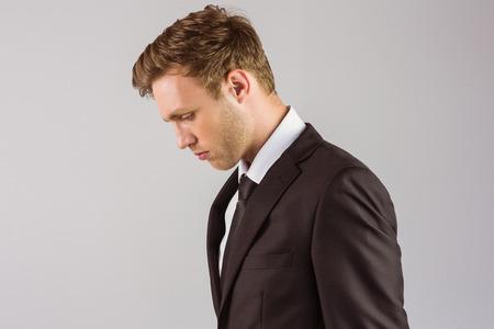 desolaci�n: Apuesto hombre de negocios joven mirando hacia abajo sobre fondo gris