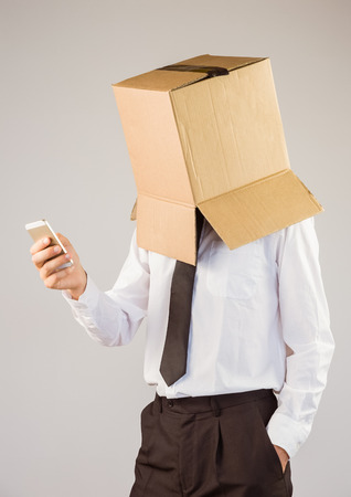 Anonymous businessman with his smartphone on grey background