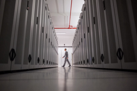 centro de computo: T�cnico de pie en el pasillo del servidor en grandes centros de datos Foto de archivo