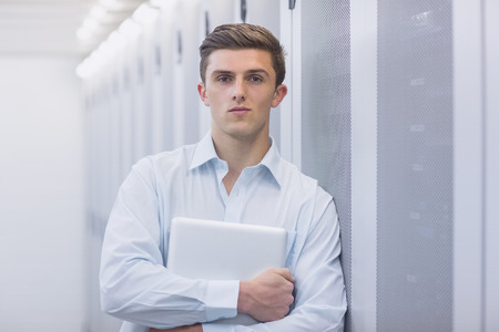 Portrait of a confident technician holding a laptop and leaning against a tower in a large data center photo