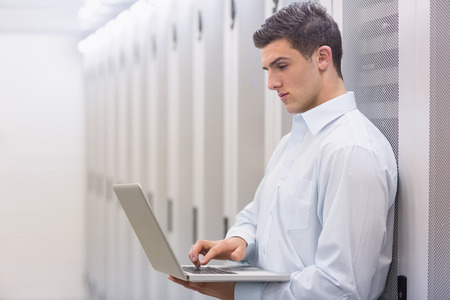 digital data: Focused technician typing on his notebook and leaning against a tower in a large data center
