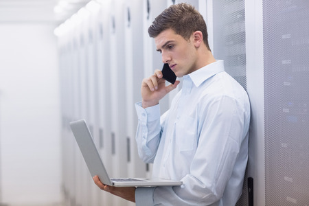 data center: Young technician phoning and using his notebook in a large data center Stock Photo