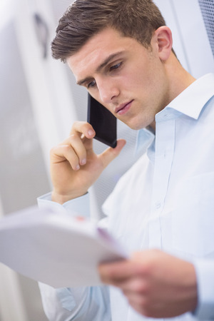 young adult men: Young technician calling and reading a document in a large data center Stock Photo