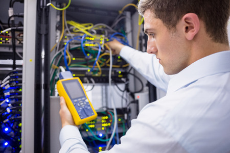 computer programmer: Serious technician using digital cable analyzer on server in large data center Stock Photo