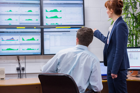 Focused colleagues analyzing result on their computer in office running diagnostics in large data center