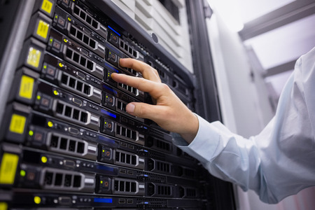 Technician working on server tower in large data center photo