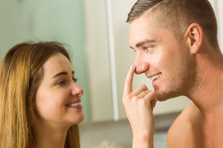 rubbing noses: Cute woman putting cream on boyfriends nose at home in the bathroom Stock Photo