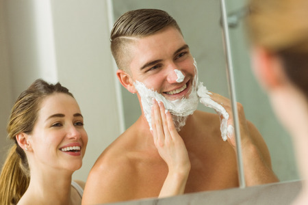 Woman putting shaving foam on boyfriends face at home in the bathroom photo