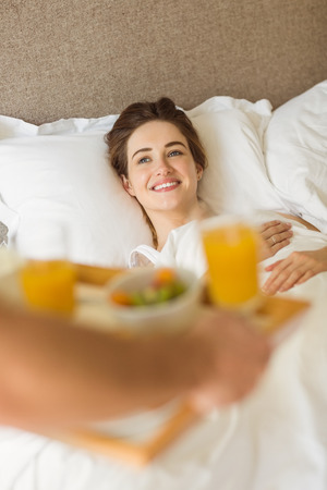 spoiling: Cute couple having breakfast in bed at home in the bedroom