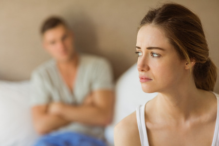 woman serious: Upset couple not talking to each other after fight at home in the bedroom