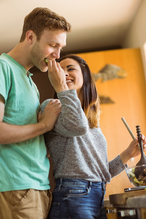 fashionable couple: Cute couple making a salad at home in the kitchen Stock Photo