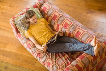 young adult men: Young man reading magazine on his couch at home in the living room