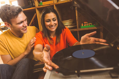 vintage living room: Young couple putting on a vinyl record at home in the living room Stock Photo