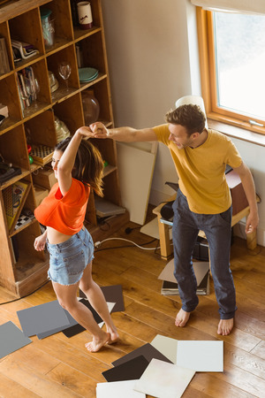 Young couple dancing to vinyl records at home in the living room photo