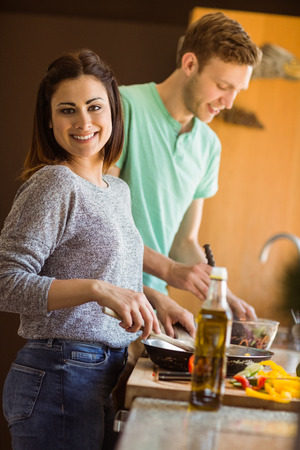 Cute couple preparing food together at home in the kitchen photo