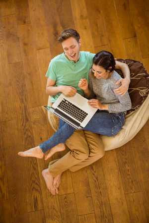 beanbag: Cute couple using laptop on beanbag at home in the living room