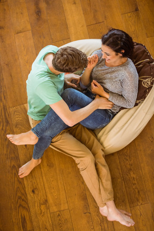 beanbag: Cute couple laughing together on beanbag at home in the living room