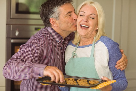 kiss biscuits: Mature blonde holding fresh cookies with husband kissing her at home in the kitchen