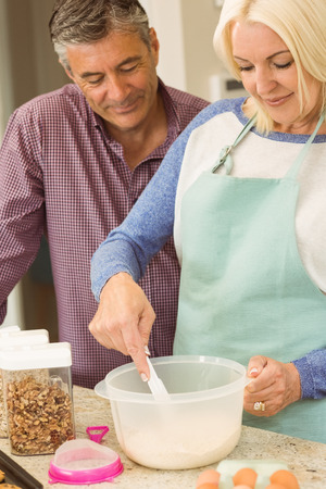 Happy blonde preparing dough with husband at home in the kitchen photo