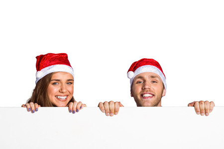Portrait of happy young couple in santas hats with blank board over white background photo