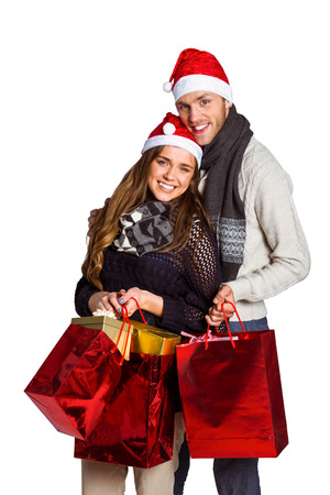 Portrait of happy young couple in santas hats with gifts over white background photo