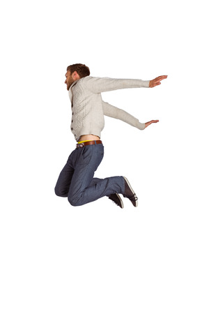 air jump: Full length of cheerful young man jumping over white background