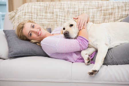Beautiful blonde on couch with pet dog at home in the living room photo