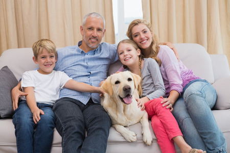 Parents and their children on sofa with labrador at home in the living room photo