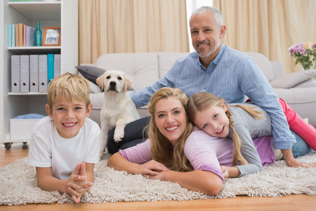 Happy parents and their children on floor with puppy at home in the living room Stock Photo