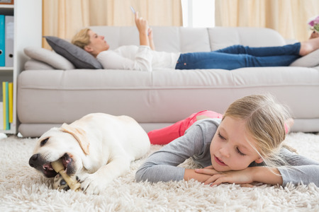 animal family: Happy little girl with her puppy at home in the living room Stock Photo