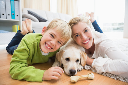 Happy mother and son with puppy at home in the living room photo