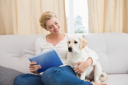 Happy blonde using tablet pc with puppy at home in the living room photo