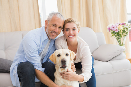 Happy couple with their pet dog at home in the living room photo