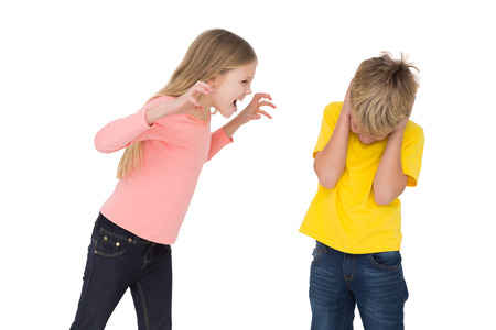 Little girl scaring her brother on white background photo