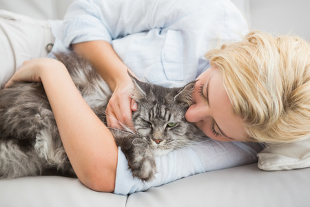 rubbing: Happy blonde with pet cat on sofa at home in the living room Stock Photo