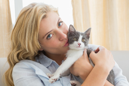 kissing love: Pretty blonde with pet kitten on sofa at home in the living room