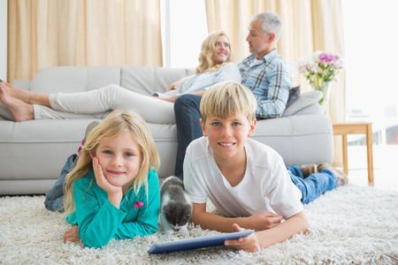 Siblings using tablet pc on the floor at home in the living room photo