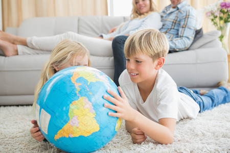 Siblings looking at globe on the floor at home in the living room photo