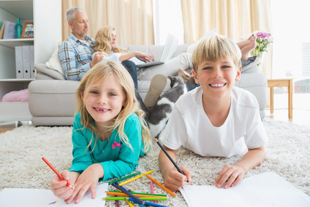 Siblings colouring and drawing on the floor at home in the living room photo