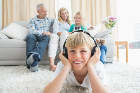 Little boy listening to music on the floor at home in the living room photo
