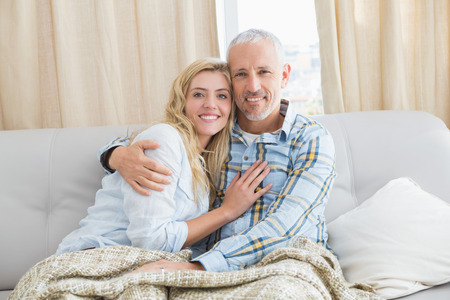 woman with camera: Happy couple relaxing on the couch at home in the living room Stock Photo