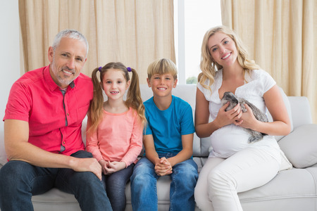 Happy family with pet bunny at home in the living room photo