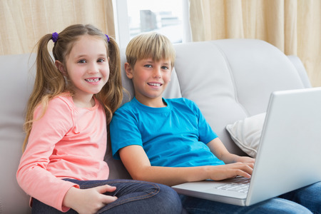 Happy siblings using laptop on sofa at home in the living room photo